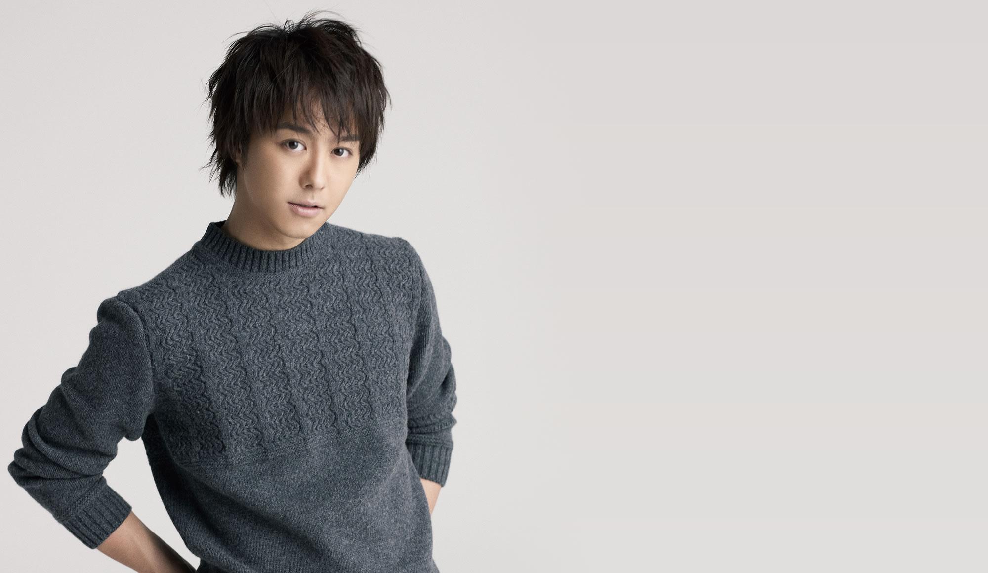 グレーのセーターを着て腰に手を当てているEXILEのTAKAHIROの画像
